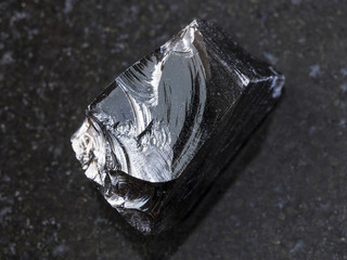 piece of raw Obsidian (volcanic glass) on dark