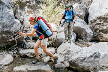 Group of friends hikers and travelers walking at Goynuk Canyon in Turkey, passing the stream, Lycian way concept