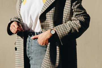 close up fashion details, young fashion blogger wearing black and white modern watch and a checked double breasted coat. ideal fall outfit accessories.