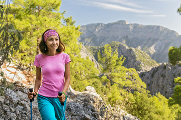 Young hiker woman standing on cliff's edge and looking into a Goynuk canyon in Turkey. Lycian Way travel concept