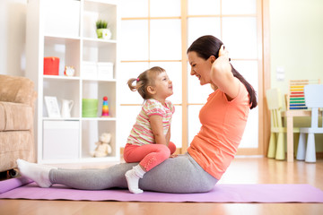 Mother and child daughter are engaged in fitness, yoga, exercise at home. Kid and woman swing press on stomach.