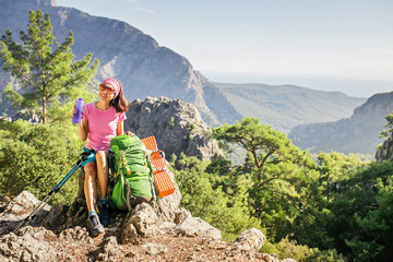 Young tourist woman is sitting on the top of the mounting and looking at a beautiful landscape, Turkey Goynuk canyon