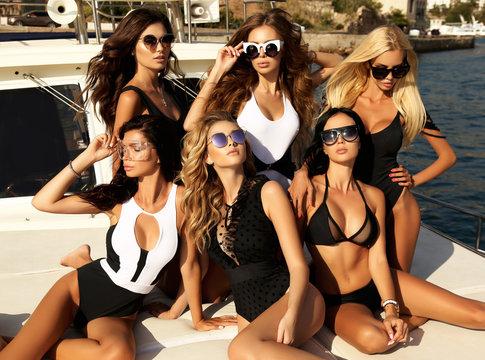 sexy girls in luxurious bikini relaxing on yacht in the sea