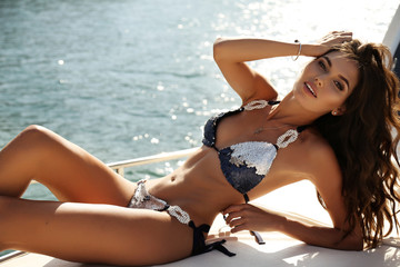 sexy girl with dark hair in luxurious bikini relaxing on yacht in the sea