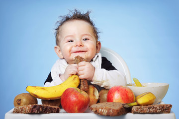 Cute Baby boy eating healthy food for breakfast on bright blue background: horizontal
