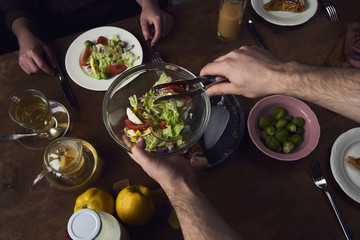 Bowl with salad in man's hand on wooden rustic background. Preparing to eating