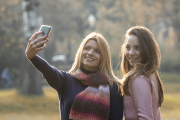 Two young girls in park taking selfie by mobile phone