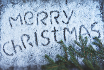 Merry christmas hand drawn lettering with christmas tree over wooden board