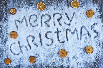 Merry christmas hand drawn lettering with orange fruit over wooden blue board