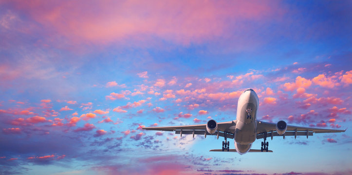 Landing airplane. Landscape with white passenger airplane is flying in the blue sky with pink clouds at sunset. Travel background. Passenger airliner. Business trip. Commercial aircraft. Private jet