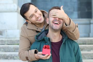 Man surprising his boyfriend with a present