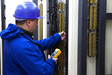 Electrician in blue control circuit with multimeter