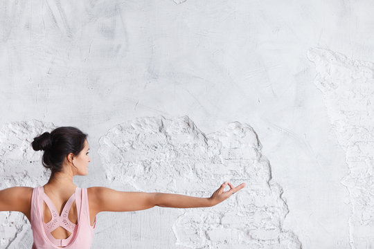 Image of woman hand in prana mudra. Gesture is on white brick wall background.