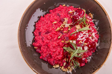 Beet орзотто with goat cheese and pine nuts, parmesan and rosemary is served with cheese