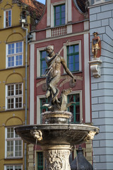 Historic Neptune Fountain, located at Long Market Street (Long Lane), in front of old buildings at the Main Town (Old Town) in Gdansk, Poland, on a sunny day.