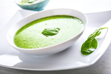 Spinach soup with green leaves in white plate