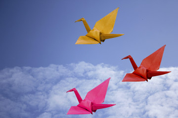 Three origami birds made from origami paper.businnes leader concept with sky background