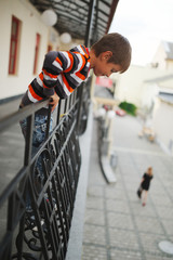 boy hanging out from the balcony