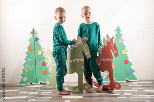 Two Funny Boys In A Santa Claus Hat Are Playing With Horses Drawn On