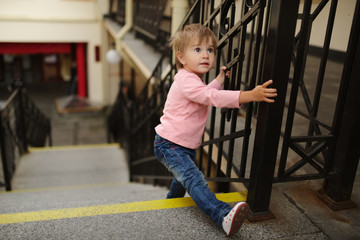 little girl climbs up on stairway