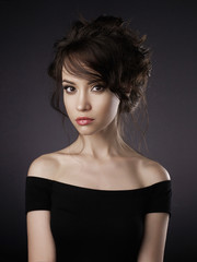 Beautiful woman with elegant hairstyle on black background