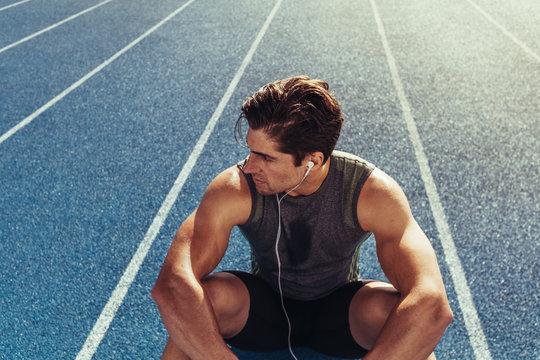 Sprinter relaxing on running track