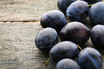 Ripe and sweet plums on wooden table