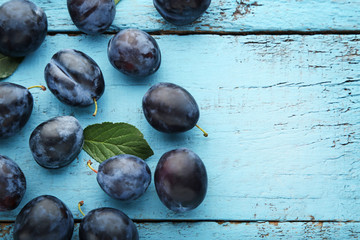 Ripe and sweet plums on blue wooden table