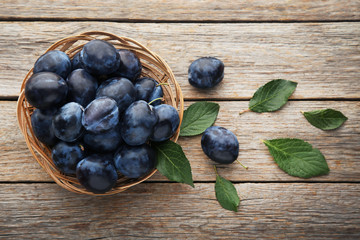 Ripe and sweet plums in basket on grey wooden table