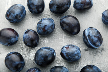 Ripe and sweet plums on grey wooden table