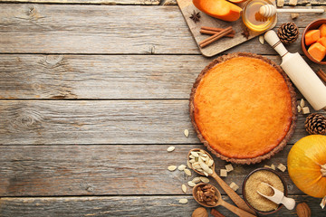 Pumpkin tart with seeds, honey and cinnamon on wooden table