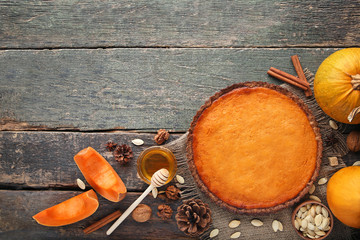 Pumpkin tart with honey, seeds and walnuts on wooden table