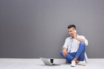 Young man with laptop and mobile phone sitting on floor near grey wall