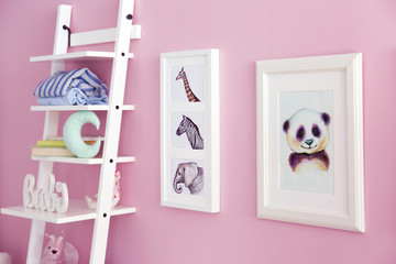 Shelves with toys and pictures of animals on wall in baby room