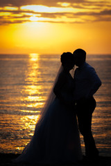 The bride and groom stand on the beach at sunset.