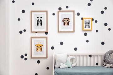 Pictures of animals on wall in baby room