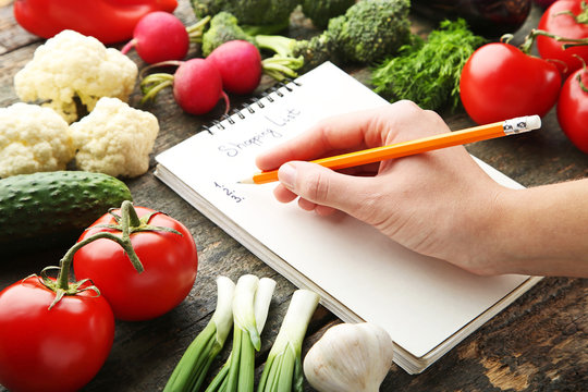 Female hand written shopping list on paper with vegetables on wooden table
