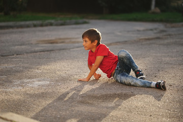 boy lying on asphalt on the street
