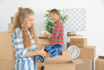 Young couple unpacking boxes in room at new home