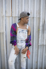 Young man in dungarees leaning on corrugated iron fence