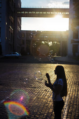 Girl with soap bubbles. Silhouette of woman in summer evening.  City street with office building in backlight. Rest after work