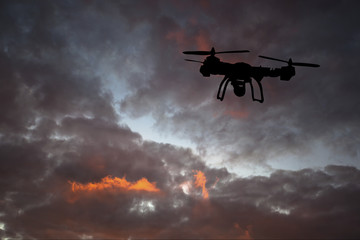 Innovation concept. Silhouette of drone flying on sunset. Heavy lift drone photographing