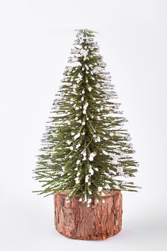 Miniature Christmas tree on white background. Decorative Christmas tree isolated on white background. Little snowy toy Christmas tree.