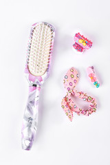 Bright accessories for girls hair. Floral print hair brush and hair holders for kids. High quality comb, rubber bands and hairpins for little girls on white background.