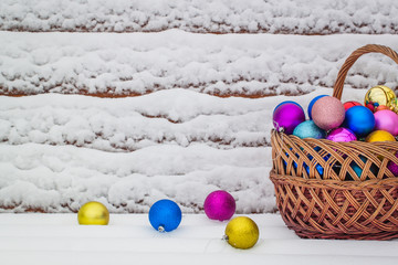 Colored Christmas-tree toys in a vintage basket on the snow