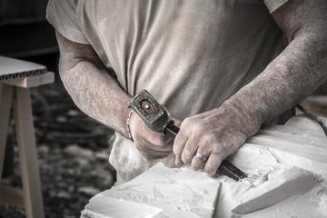 Particolare delle mani dell'artista che lavora il marmo con martello e scalpello