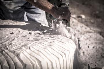Artista che scolpisce il marmo con un martello pneumatico