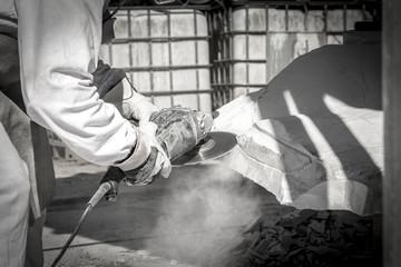 Artista che taglia il marmo con disco diamantato