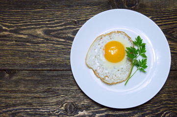 Aluminium Prints Egg Fried egg with green parsley on plate on vintage wooden background
