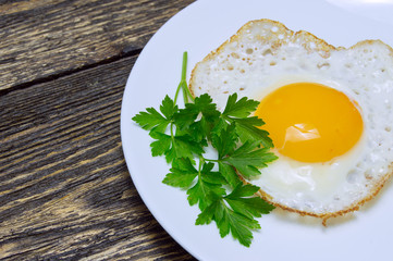 Fried egg with green parsley on plate close up, on vintage wooden background